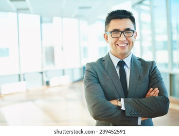 Cheerful businessman in formalwear keeping his arms crossed