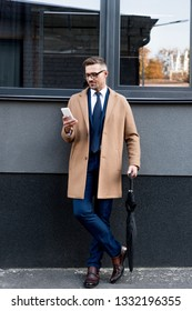 cheerful businessman in glasses looking at smartphone while standing in beige coat and holding umbrella