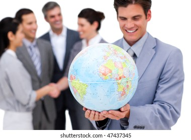 Cheerful businessman holding a globe in front of his team against a white background