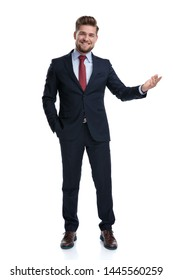 Cheerful businessman presenting with his hand in his pocket while laughing and wearing a blue suit, standing on white studio background