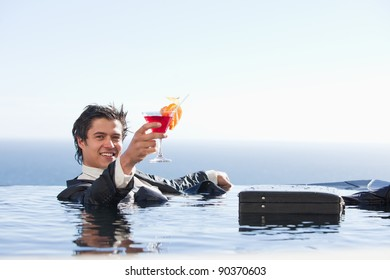 Cheerful businessman relaxing in a swimming pool with a cocktail in a suit