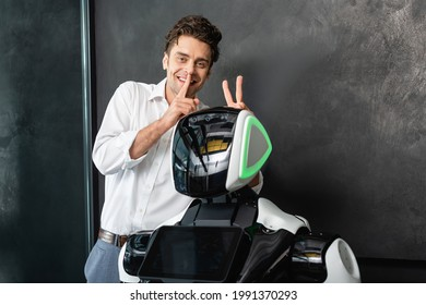 cheerful businessman showing hush gesture and bull horns sign near robot in office