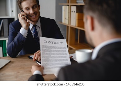 Cheerful businessman sitting with a phone near his ear while colleague with a contract in hands being opposite him