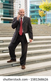 Cheerful businessman with smartphone and laptop. Full length view of happy mature businessman standing on steps with laptop computer and talking by cell phone. Technology concept