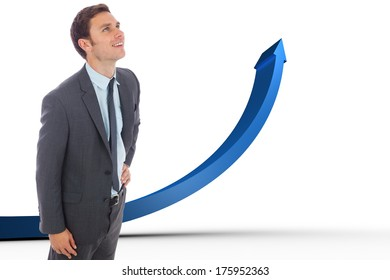 Cheerful businessman standing with hand on hip against blue arrow pointing up