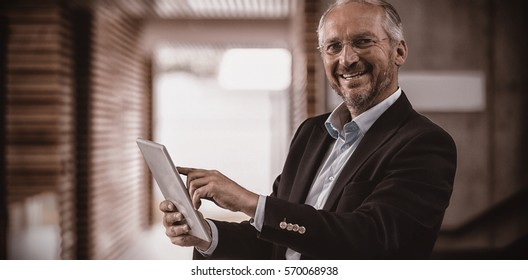 Cheerful businessman standing in office holding digital tablet