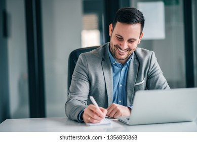 Cheerful businessman taking notes while working in the office.