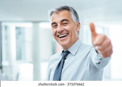 Cheerful businessman thumbs up posing and smiling at camera