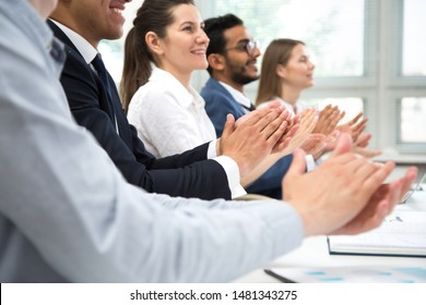 Cheerful businesspeople clapping hands at business seminar.