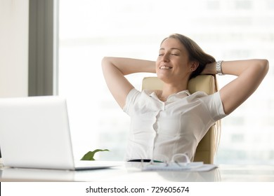Cheerful businesswoman dreaming at workplace. Smiling girl leaning back in chair with hands behind head and closed eyes. Female office worker takes break after job done. Business lady relaxing at work