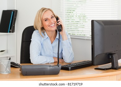 Cheerful businesswoman on phone looking into camera in her office
