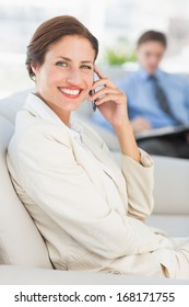 Cheerful businesswoman on the phone sitting on couch in the office
