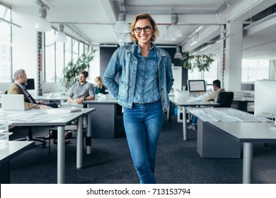 Cheerful businesswoman standing in office environment. Young female executive standing and looking at camera.