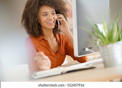 Cheerful businesswoman talking on phone in office