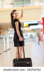 cheerful businesswoman waving goodbye at international airport