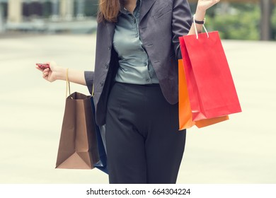 Cheerful businesswoman wear suit holding shopping bags, shopaholic woman with colorful shopping bags walking on terrace at modern city, Shopping concept