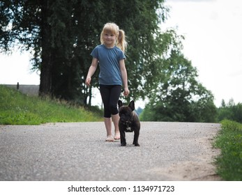 Cheerful carefree girl and dog go on a rural road. Barefoot baby