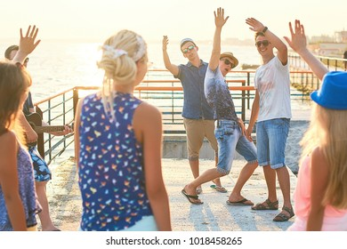 Cheerful and carefree group of friends both girls and guys hanging out at the sunny summer seaside on their vacation