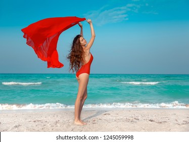 Cheerful carefree woman brunette girl in red bikini with blowing sarong enjoying on the beach. Wellness. Summer holiday outdoor vacation.
