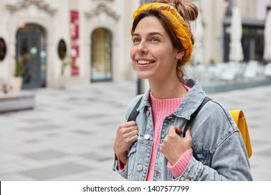 Cheerful carefree woman dressed in fashionable outfit, has charming smile on face, enjoys recreation time, carries small rucksack, strolls across city, being in good mood. Vacation, traveling