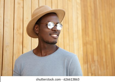 Cheerful carefree young dark-skinned man wearing mirrored lens shades and trendy hat smiling happily, rejoicing at warm sunny weather, posing isolated at wooden wall with copy space for your content