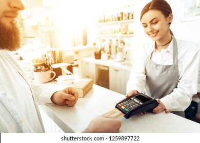 Cheerful cashier using digital device for payment. A smiling girl waiter calculates a bearded man in a cafe with a bank card. The concept of the restaurant business and service maintenance