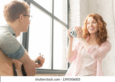 Cheerful casual girl with photocamera photographing her friend playing guitar and singing at home party