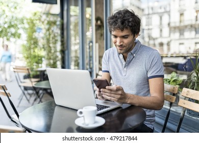 Cheerful casual man working on laptop in cafe terrace. Businessman texting on smartphone outdoor in the city