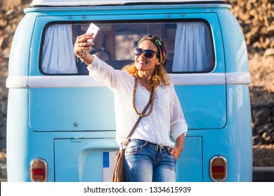 Cheerful caucasian 40 years old woman smile and take a selfie picture with phone cell - fashion trend happy people outdoor enjoying lifestyle - old vintage bus blue in background