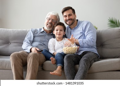 Cheerful caucasian 60s grandfather grown up son and little grandchild sitting on couch use remote control watching movie eating pop corn, boyish hobbies, different age football fans enjoy game on TV