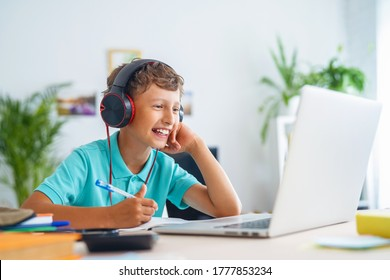 cheerful Caucasian boy with headphones uses laptop to make video call with his teacher. child is happy to learn remotely. He happy to receive knowledge. E-Education Distance Learning, Home Schooling. - Shutterstock ID 1777853234