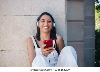 Cheerful caucasian brunette woman meloman excited with new app on smartphone for playlist songs outdoors, happy female 20s using mobile phone and headphones listening favorite music entertaining