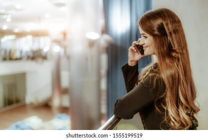A cheerful caucasian businesswoman is phoning while leaning the railing of a balcony of an office open-space area; a charming mature smiling woman entrepreneur having phone conversation indoors