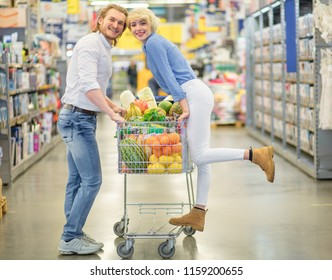 Cheerful caucasian family with pushcart, filled with vegetables and fruits standing in the mall passage between rows of shelves, looking at camera.