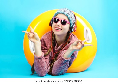Cheerful caucasian girl in warm winter clothes listening music on headphones with an inflatable orange circle for swimming on blue background. Concept summer vacation.