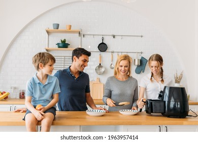 Cheerful caucasian handsome father and beautiful mother with son and daughter preparing healthy snacks in kitchen using air fryer at home