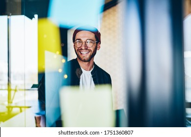 Cheerful caucasian hipster guy in trendy eyewear satisfied with creative job laughing sitting near stickers with ideas in office, 20s smiling carefree male student enjoying learning in business school