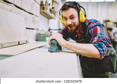 Cheerful caucasian male owner in protective equipment making polish with sander satisfied with his small businessin manufactory, skilled bearded guy using grinder on carpentry courses making furniture