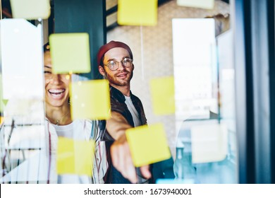 Cheerful caucasian male pointing on sticker with ideas having brainstorming session with diverse group of employees, smiling asian girl satisfied with creative working process and team collaboration
