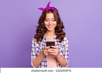 Cheerful charming careless carefree lady in checkered shirt casual wear with her brunette modern hairdo she hold cellular send message to friends isolated on bright violet background