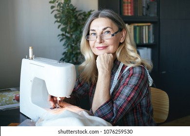 Cheerful charming mature woman dressmaker creating new fashionable styles, working on sewing machine, feeling happy and inspired. Fashion, haute couture, clothing, garmen, apparel and tailoring