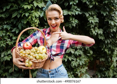 Cheerful charming pin up girl pointing on basket of fresh fruits
