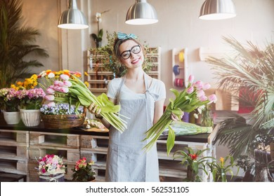 Cheerful charming young woman florist standing and holding two bunches of pink tulips in flower shop