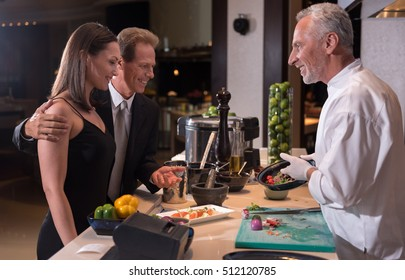 Cheerful chef advising the dish to the couple
