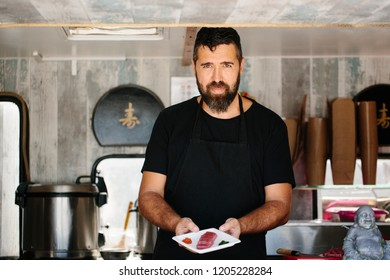 Cheerful chef in black apron serving plate with tuna†and caviar working in street food truck