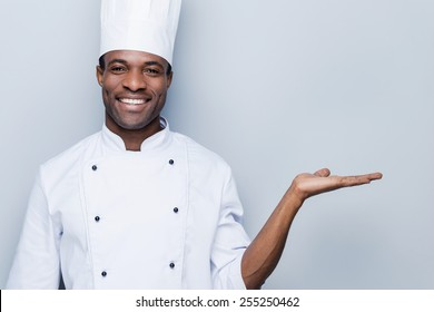 Cheerful chef. Confident young African chef in white uniform holding copy space and smiling while standing against grey background