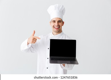Cheerful chef cook wearing uniform standing over white background, holding bank screen laptop computer