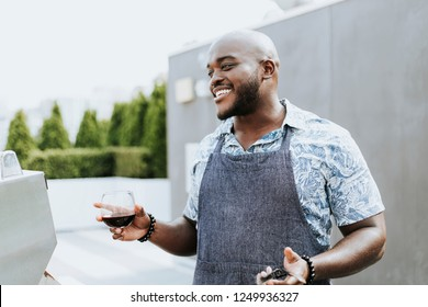 Cheerful chef with grilling tongs and a wine glass