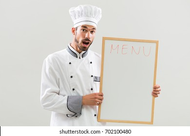 Cheerful chef showing whiteboard on gray background.Excited chef menu suggestion
