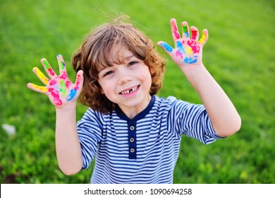 cheerful child boy with curly hair without front milk tooth shows hands dirty with multi-colored finger paints and smiles.